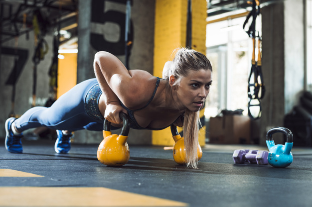 athletic-woman-doing-push-ups-kettle-ball_23-2147949601